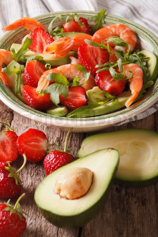 Stock image of 'Cocktail salad with strawberries, avocado, shrimp and arugula close-up on a plate. Vertical\'
