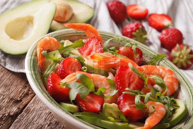 Stock image of 'Summer salad with strawberries, avocado, shrimp and arugula close-up on a plate. horizontal\'