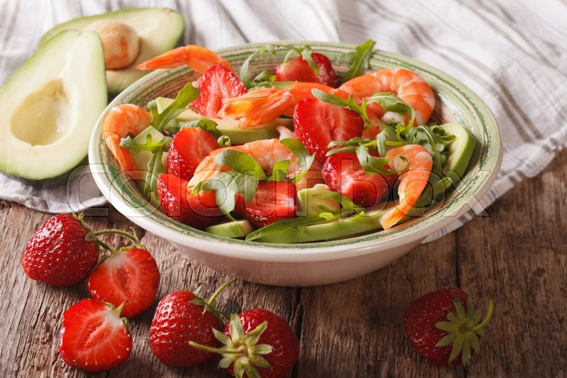 Stock image of 'Cocktail salad with strawberries, avocado, shrimp and arugula close-up on a plate. horizontal\'