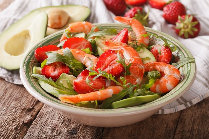 Stock image of 'Fresh salad with strawberries, avocado, shrimp and arugula close-up on a plate. horizontal\'