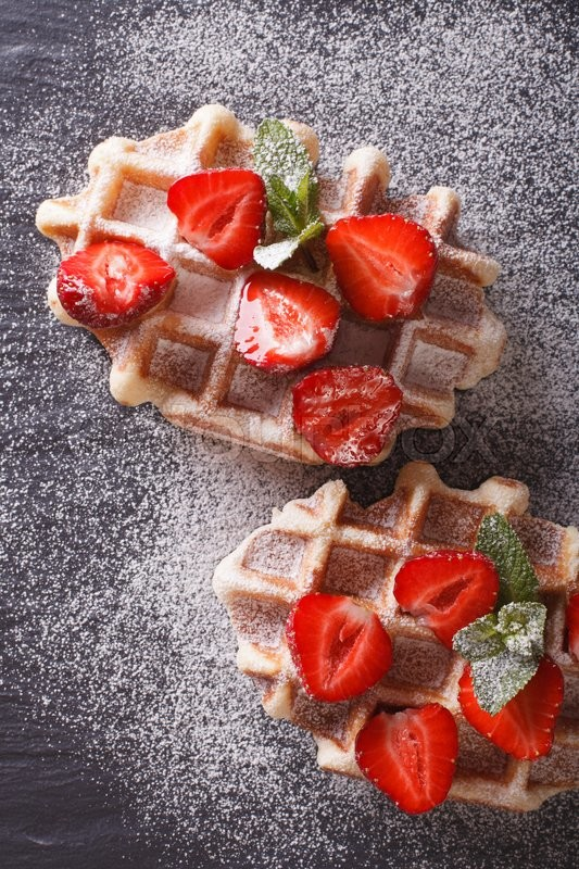 Stock image of 'Liege waffles with fresh strawberries, powdered sugar close-up on the slate. vertical view from above\'