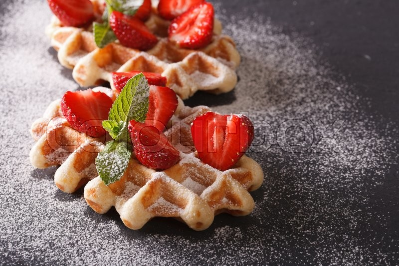 Stock image of 'Tasty dessert: waffles with fresh strawberries, powdered sugar close-up on the slate. horizontal\'