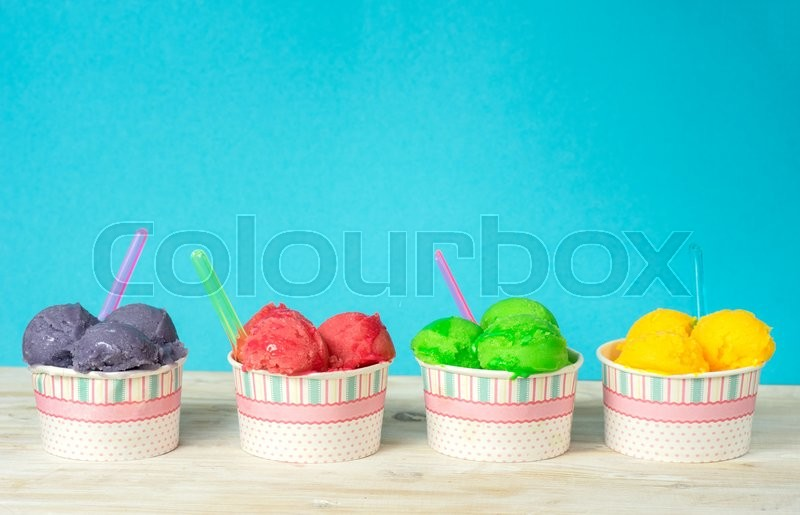 Stock image of 'Delicious fruit ice sobet in paper cups on vintage blue background'
