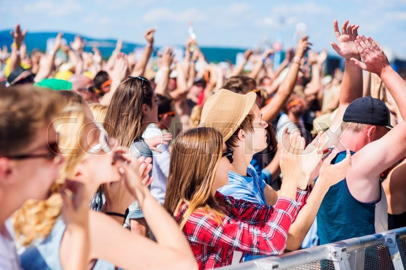 Stock image of 'Teenagers at summer music festival under the stage in a crowd enjoying themselves, whistling, clapping, singing'
