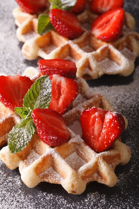Stock image of 'Belgian waffles with fresh strawberries, mint and sprinkled with powdered sugar macro on the slate. vertical\'