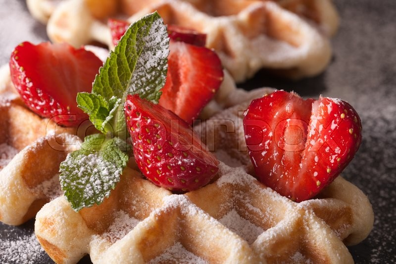 Stock image of 'Beautiful food: Belgian waffles with fresh strawberries and mint macro on the slate table. Horizontal\'