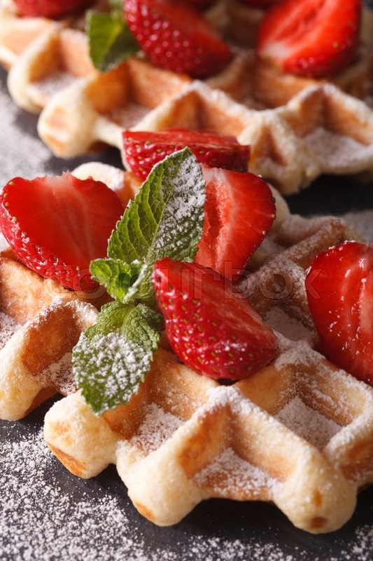 Stock image of 'Beautiful food: Belgian waffles with fresh strawberries and mint macro on the slate table. vertical\'