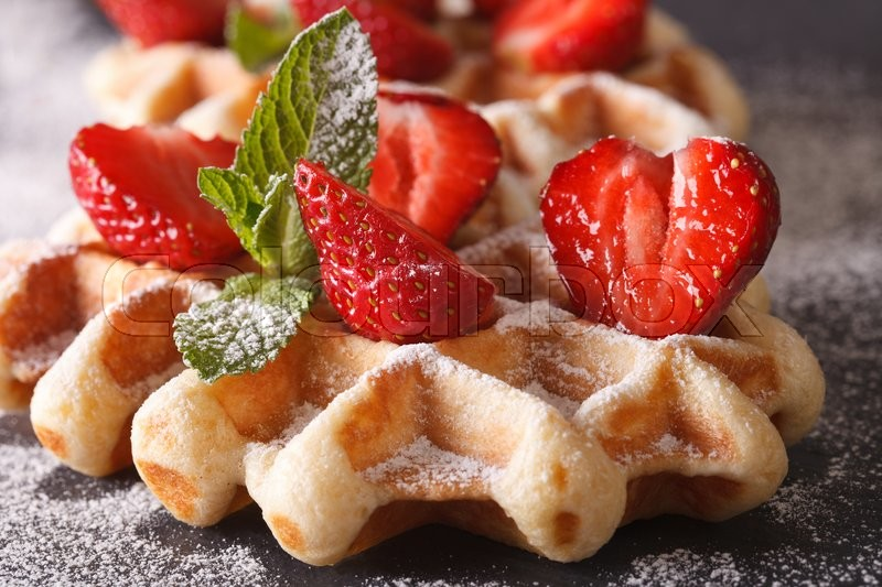 Stock image of 'Belgian waffles with fresh strawberries and mint macro on the slate table. Horizontal\'