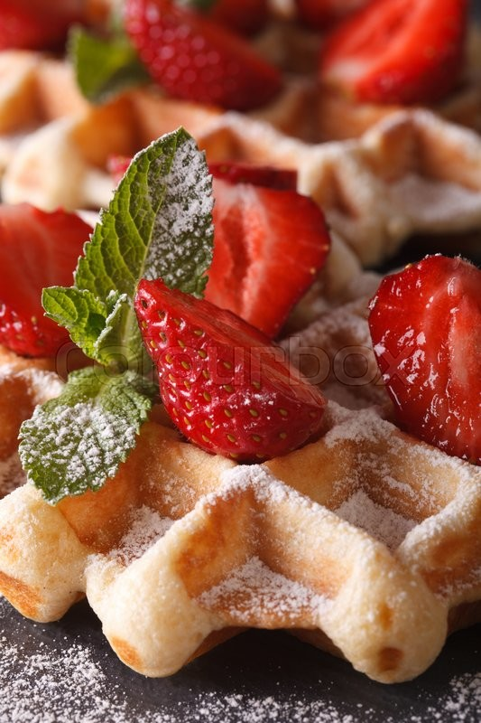 Stock image of 'Belgian waffles with fresh strawberries and mint macro on the slate table. vertical\'