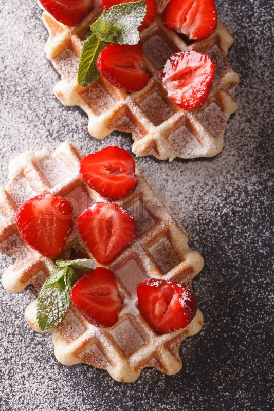Stock image of 'Belgian waffles with fresh strawberries, powdered sugar and mint close-up on the table. vertical view from above\'
