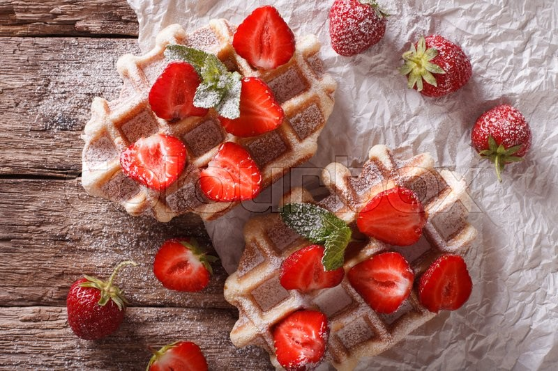 Stock image of 'rustic Belgian waffles with strawberries, powdered sugar and mint close-up on the table. Horizontal view from above\'