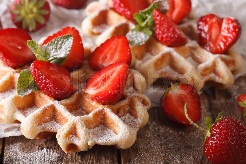 Stock image of 'Belgian cuisine: waffles with strawberries, powdered sugar and mint on a table macro. horizontal\'