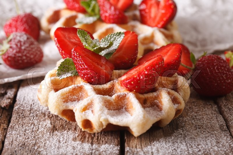 Stock image of 'Belgian waffles with strawberries and powdered sugar close-up on the table. horizontal, macro\'