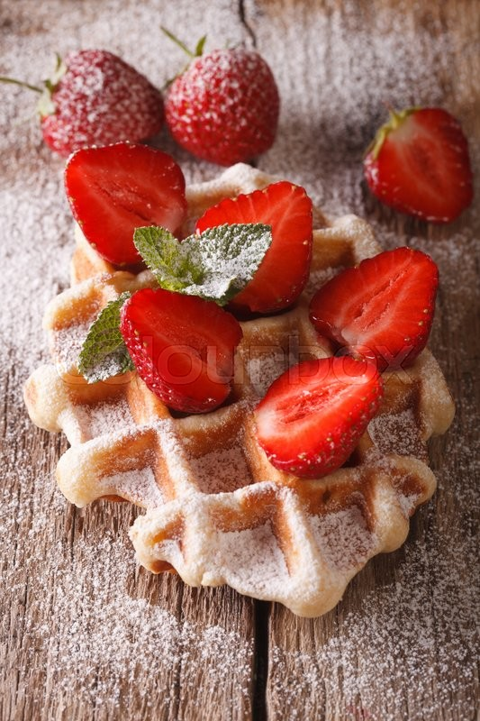 Stock image of 'Belgian waffles with strawberries and powdered sugar close-up on the table. vertical\'