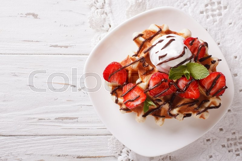 Stock image of 'Belgian waffles with strawberries and chocolate topping on a plate. Horizontal view from above\'