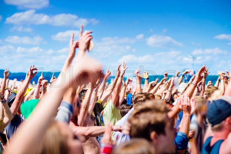Stock image of 'Teenagers at summer music festival under the stage in a crowd enjoying themselves, clapping and singing'