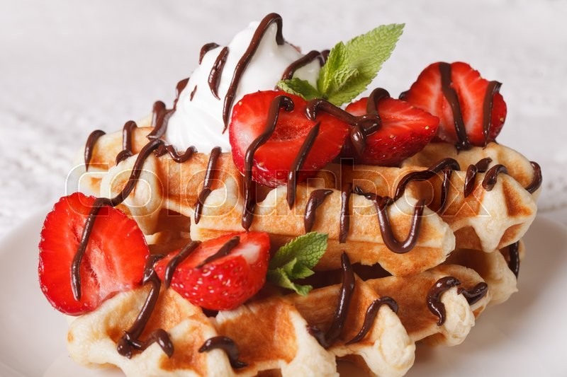 Stock image of 'Belgian waffles with strawberries, whipped cream and chocolate topping macro. Horizontal\'