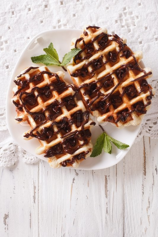 Stock image of 'Tasty Belgian waffles with chocolate topping on a plate close-up on the table. vertical view from above\'
