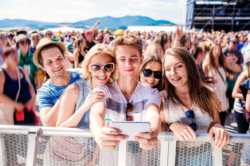 Stock image of 'Teenagers at summer music festival in crowd taking selfie with smartphone, enjoying themselves'