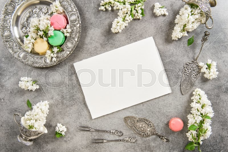 Stock image of 'Macaroon cakes and note paper for text or recipe. Vintage style background with white lilac flowers'
