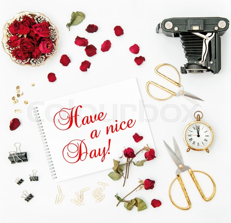 Stock image of 'Flat lay with sketchbook, red rose, vintage camera, scissors on white background. Red flowers. Have a nice Day!'