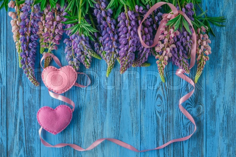 Stock image of 'valentine's day background with heart and red ribbon on blue wooden table wirh flowers'