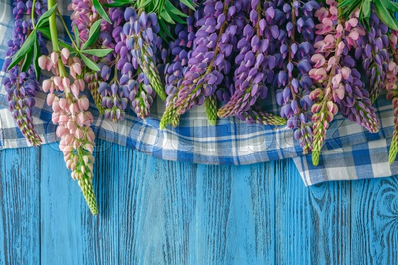 Stock image of 'Frame of lupines on turquoise rustic wooden background. Spring flowers. Spring background. Top view.'