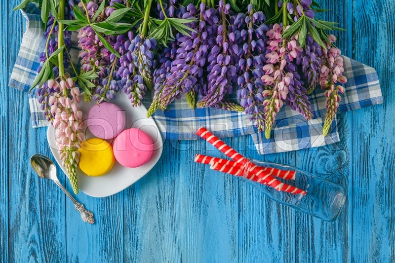 Stock image of 'Summer colorful flowers on vintage wooden background with sweets'