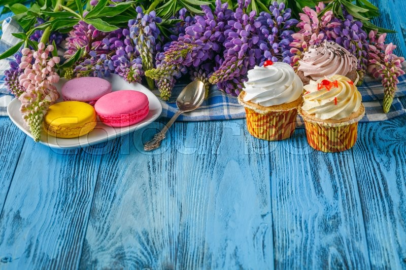 Stock image of 'Beautiful flowers on wooden background, floral background, flower border with cupcakes'
