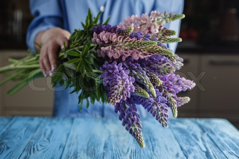 Stock image of 'Woman with bouquet of wild lupin flowers'