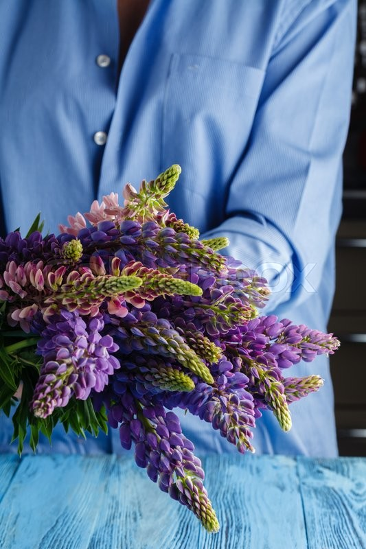 Stock image of 'Woman with bouquet of wild lupin flowers at home'