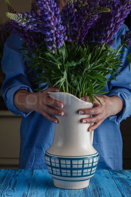 Stock image of 'Woman arranges spring flower bouquet in a vase'