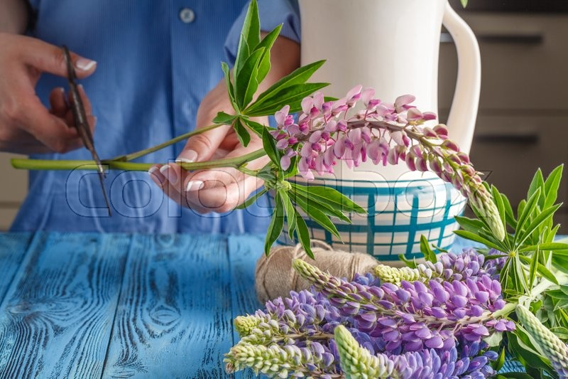 Stock image of 'Pretty Caucasian young woman arranging flowers in vase in kitchen'