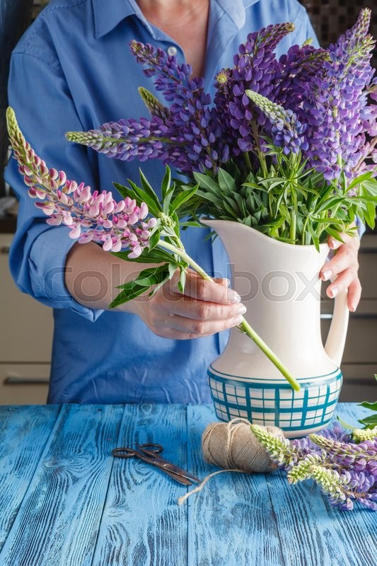 Stock image of 'Woman arranging a bunch of flowers in a vase'