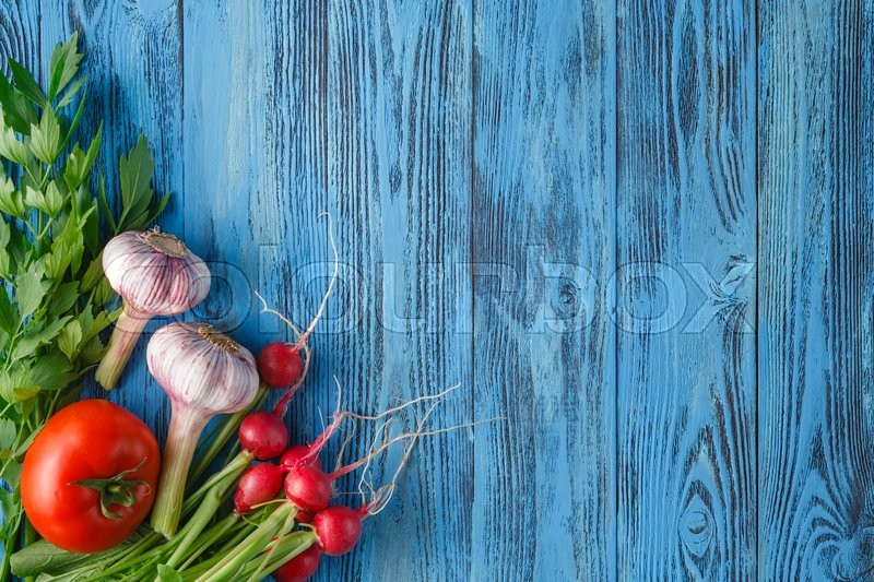 Stock image of 'Vegetables set with garlic, tomatoes and radish on wooden background with copy space'
