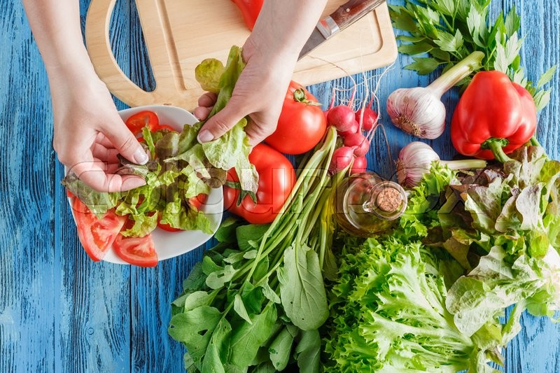 Stock image of 'Cook is tearing lettuce while making fresh summer salad, closeup shoot'