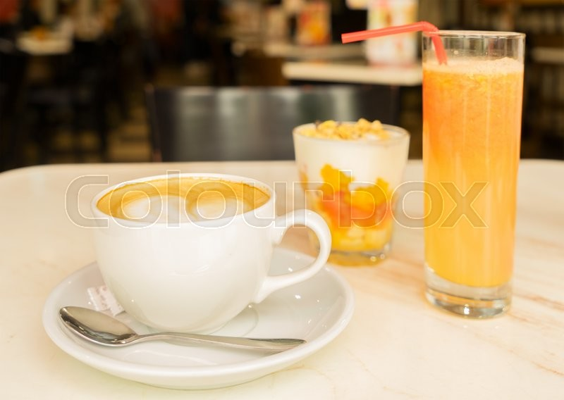 Stock image of 'Breakfast with coffee and fresh orange juice and yogurt with granola'