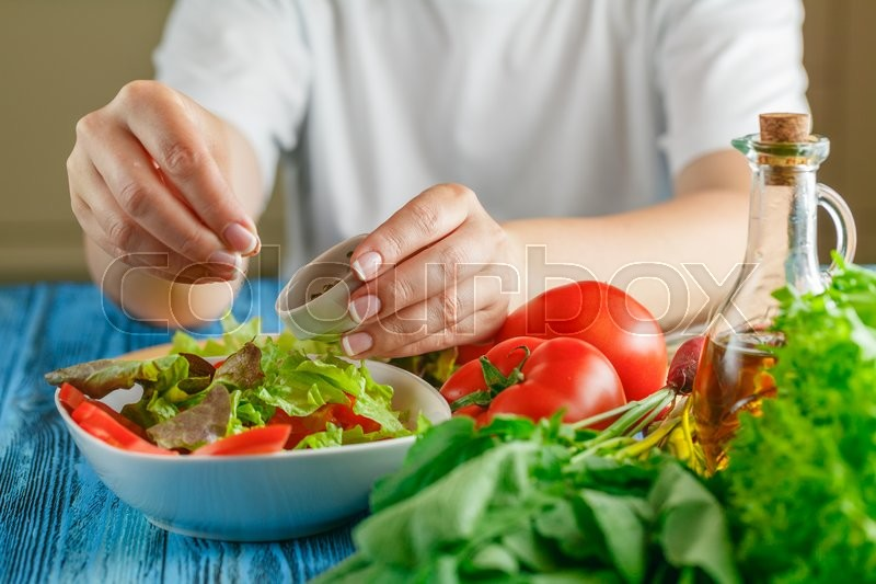 Stock image of 'Woman's hands adding spices for a vegetable salad'