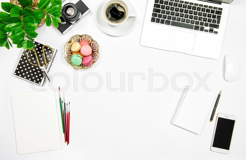 Stock image of 'Creative home office workplace. Coffee, macaroon cakes, laptop computer and green plant on white table background. Flat lay'