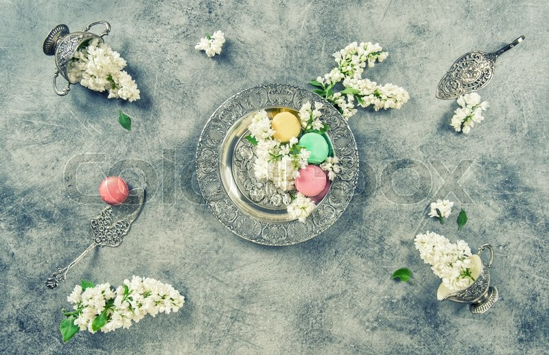 Stock image of 'White lilac flowers and macaroon cakes. Antique silver dishes. Vintage style toned picture'