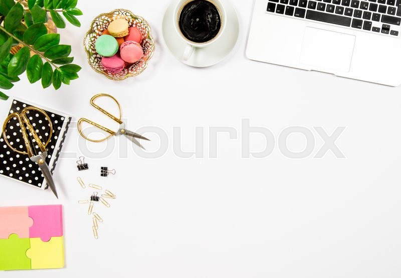 Stock image of 'Feminine office desk workplace. Coffee, cookies, laptop computer and gren plant on white table background. Top view. Flat lay'