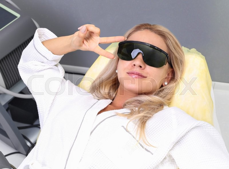 Stock image of 'Beautiful young woman is getting facial mask at spa. She is lying and relaxing. Her eyes are closed with pleasure. The cosmetologist is applying cream on her face.'