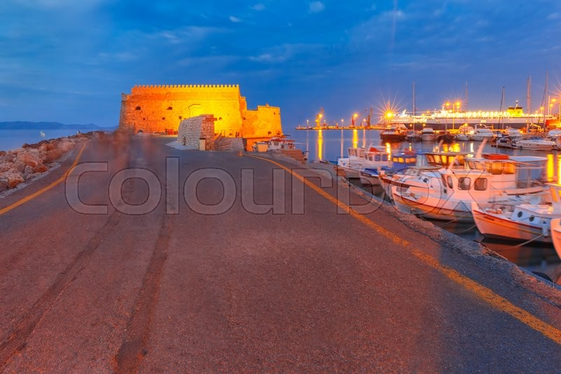 Stock image of 'Old harbour of Heraklion with Venetian Koules Fortress, boats and marina during blue hour, Crete, Greece. Boats blurred motion on foreground.'