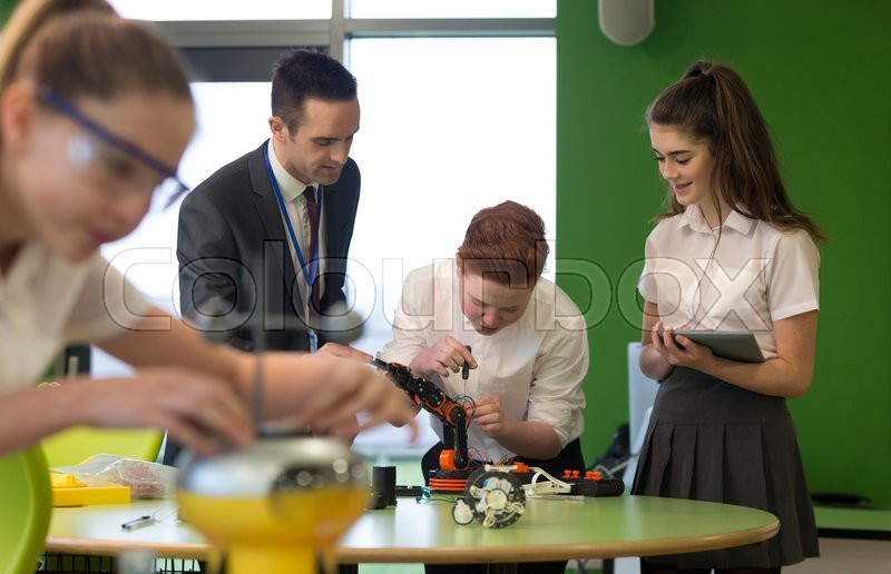 Stock image of 'Students are building a robotic arm in school. The teacher is helping them and they are following instructions from a digital tablet.'