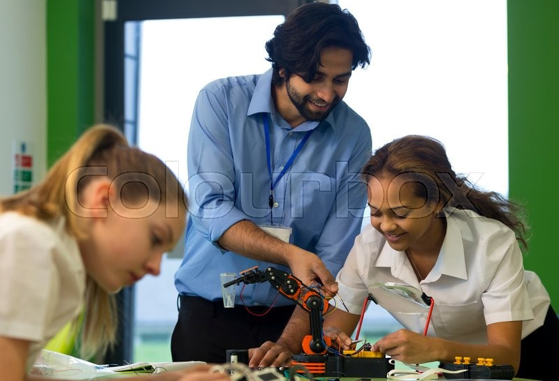 Stock image of 'Two students are building a robotic arm in school. The teacher is helping one of them. '