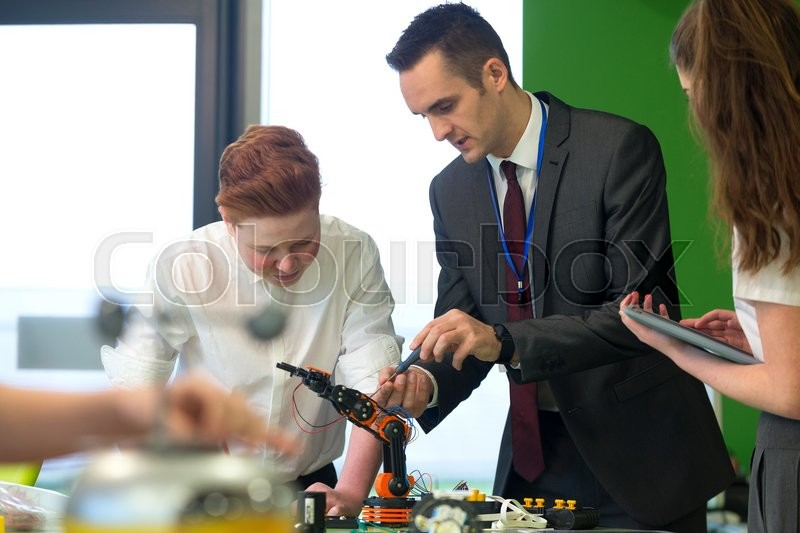 Stock image of 'Two students are building a robotic arm in school. The teacher is helping them and they are following instructions from a digital tablet.'