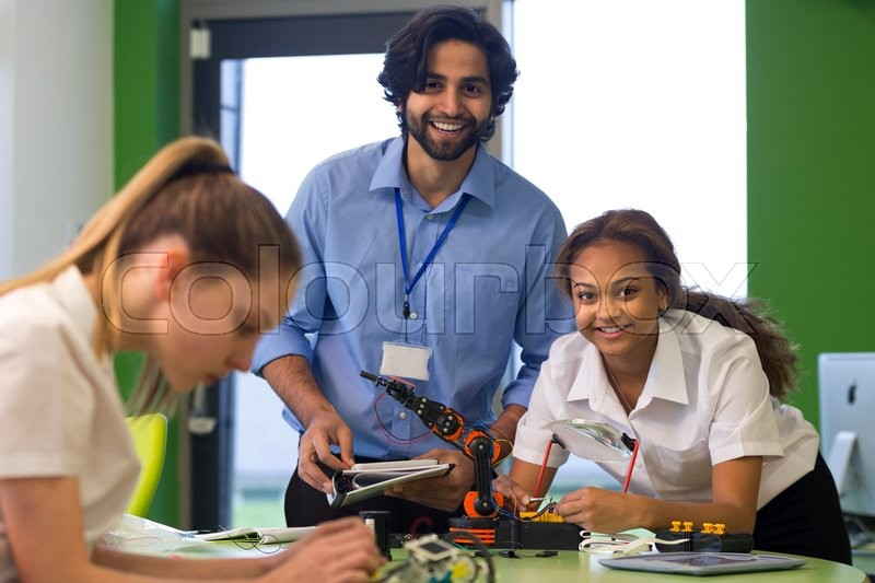 Stock image of 'Teacher and student smiling for the camera whilst building a robotic arm. Another student is out of focus in the foreground.'