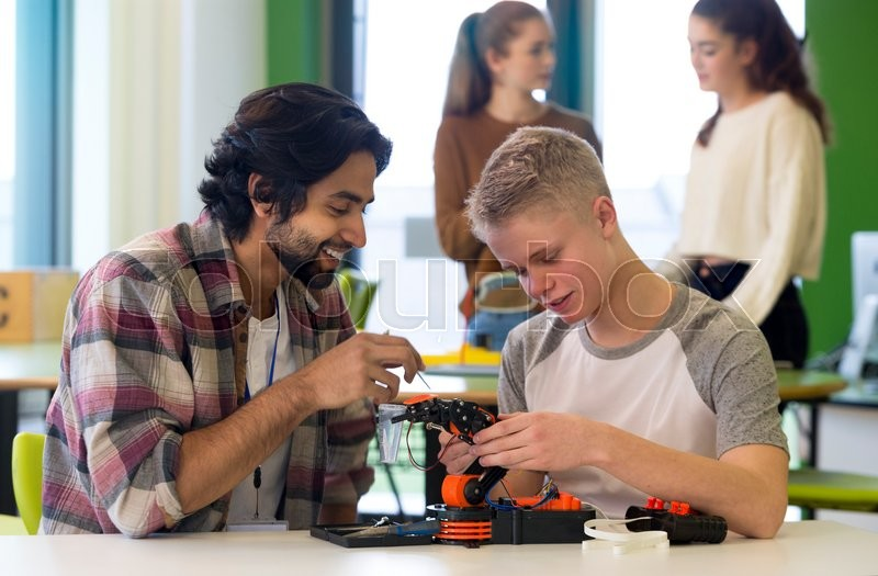 Stock image of 'Student and teacher working on a robotic arm in a classroom. There are students standing in the background.'