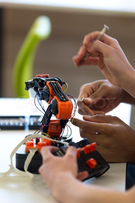 Stock image of 'Close up shot of students hands working on a robotic arm.'