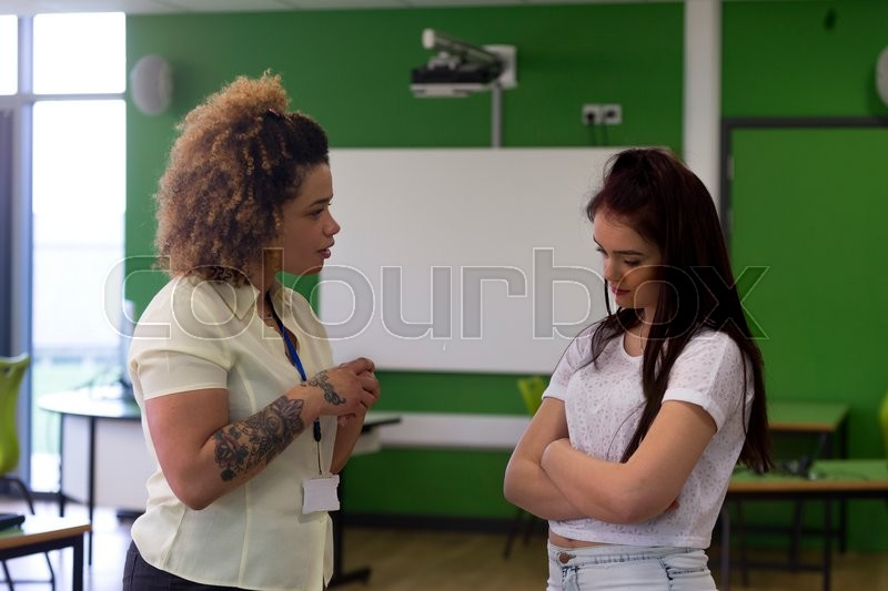 Stock image of 'Teenage student being told off by her teacher at school. '